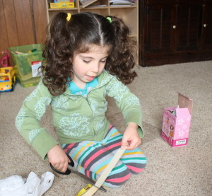 Lucy creating her contraption from an old box and tissue paper.