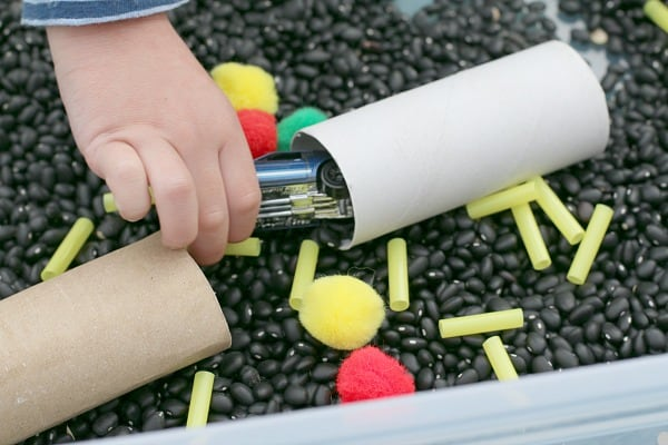 Cars traveling through cardboard tubes in the car themed sensory bin