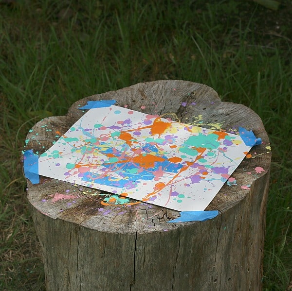 splatter paint drying outside on tree stump