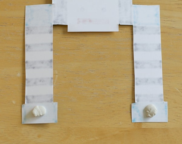 place poster putty on hands of paper robot