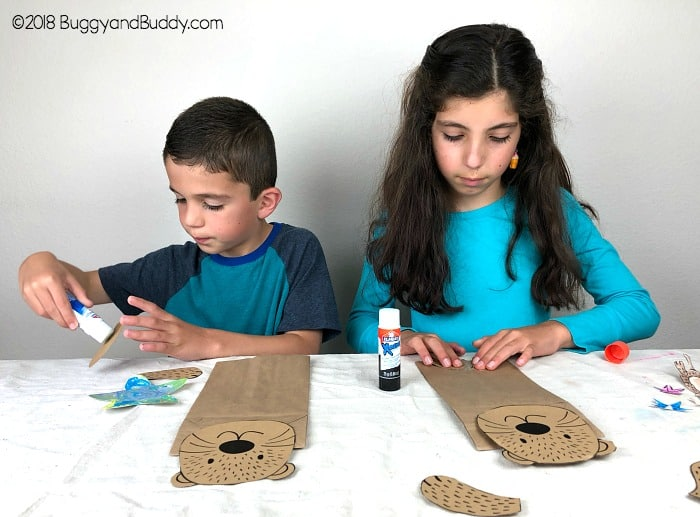 glue your sea otter pieces to the paper bag to make your puppet